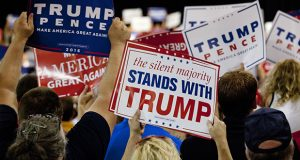 Attendees wave signs Aug. 19 for Republican presidential nominee Donald Trump as he speaks during a campaign event in Lansing, Michigan. (Bloomberg file photo)