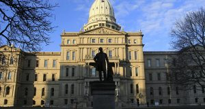 A statue of Michigan Gov. Austin Blair, who served 1861-1864, is silhouetted against the state Capitol in Lansing, Michigan. Democrats this year are seeking to wrest control of as many as a dozen legislative chambers from Republicans across the country. (AP file photo)